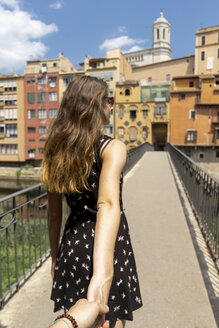 Spain, Girona, woman holding man's hand walking in the city - AFVF00809
