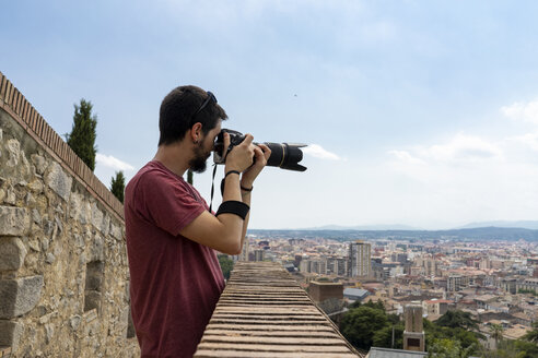 Spain, Girona, man at the castletaking picture of the city - AFVF00815
