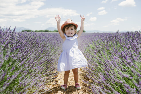 France, Provence, Valensole plateau, Happy toddler girl standing in purple lavender fields in the summer - GEMF02132
