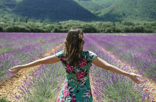 France, Provence, Valensole plateau, woman standing with outstretched arms in lavender fields in the summer - GEMF02153