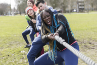 Determined team pulling rope in tug-of-war at park - CAIF21190