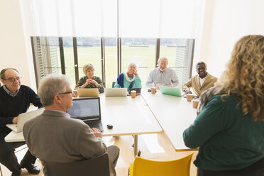 Senior business people using digital tablets and laptops in conference room meeting - CAIF21274