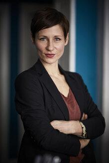 Portrait of a businesswoman leaning in door - RBF06428