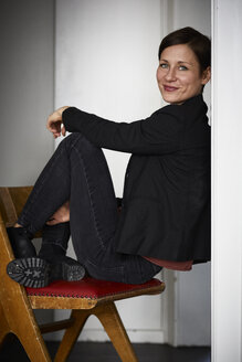 Modern woman crouching on chair, leaning on wall - RBF06434