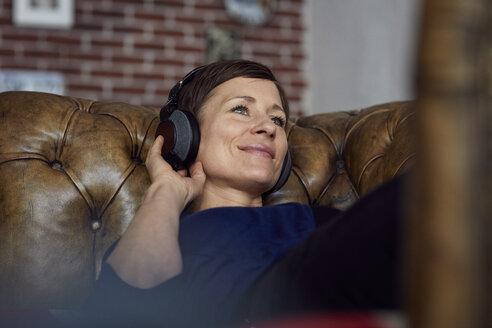 Woman with headphone lying on sofa, listening music - RBF06440