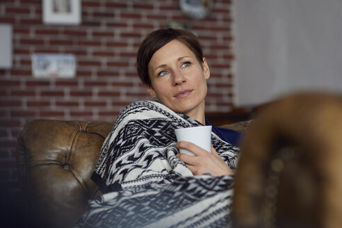 Woman on sofa relaxing at home, drinking tea - RBF06446