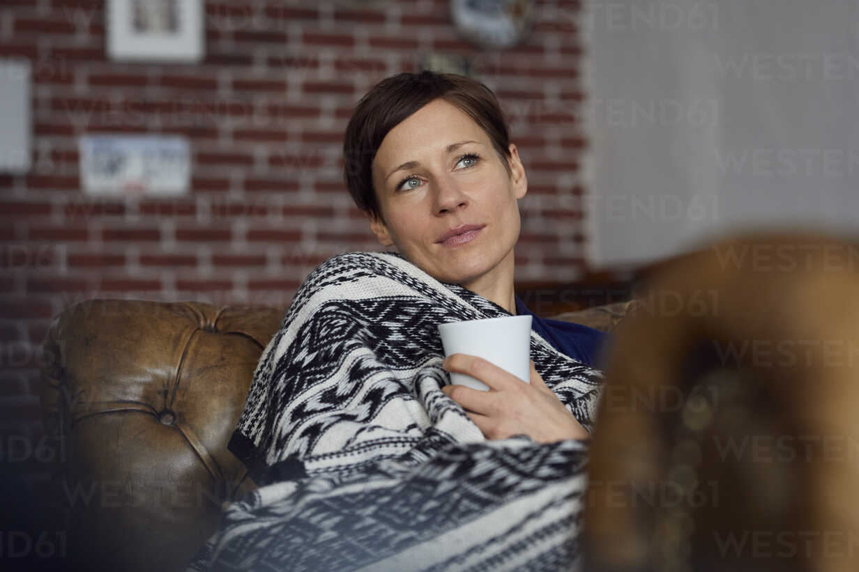 Woman on sofa relaxing at home, drinking tea - RBF06446 - Rainer Berg/Westend61