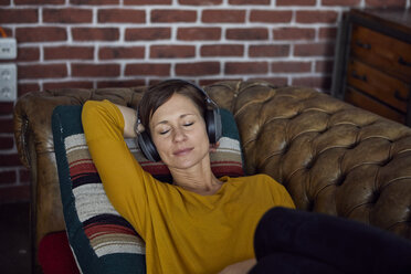 Woman with headphone lying on sofa, listening music - RBF06449