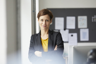Attractive businesswoman standing in office with arms crossed - RBF06458