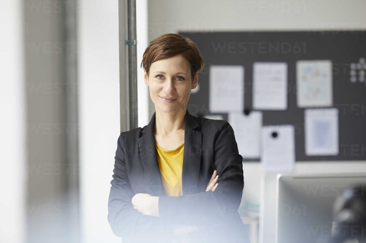 Attractive businesswoman standing in office with arms crossed - RBF06458 - Rainer Berg/Westend61