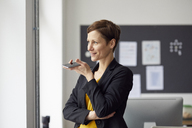 Attractive businesswoman standing in office, using smartphone - RBF06461