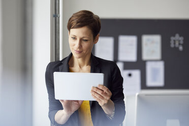Attractive businesswoman standing in office, using digital tablet - RBF06464