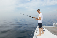 Mature man standing on catamaran, fishing - EBSF02576