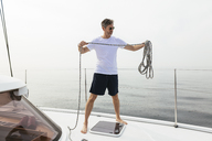 Mature man standing on catamaran, coiling rope - EBSF02579