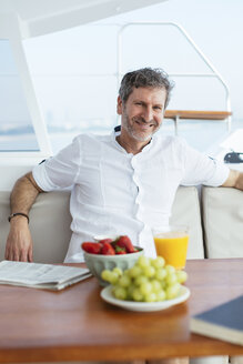 Mature man on a sailing trip having a healthy breakfast, reading newspaper - EBSF02591