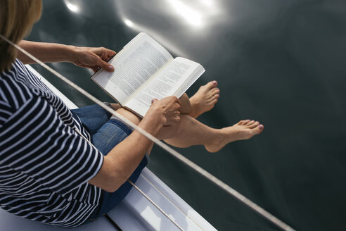 Woman sitting on sailing boat, reading a book - EBSF02594