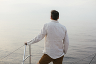 Marure man on catamaran, looking ta view - EBSF02597