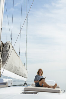 Woman sitting on deck of a catamaran, reading a book - EBSF02600