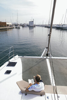 Mature man sitting on a catamaran, reading book - EBSF02612