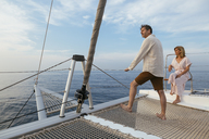 Mature couple standing on catamaran trampoline, enjoying their sailing trip - EBSF02615