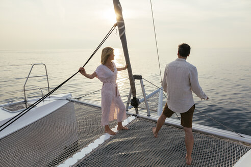 Mature couple standing on catamaran trampoline, enjoying their sailing trip - EBSF02621