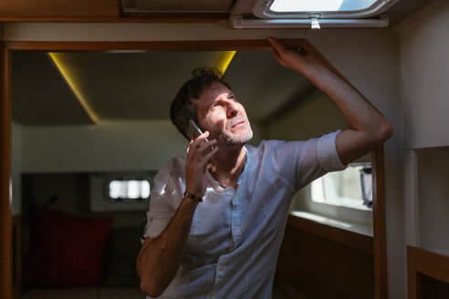 Mature man standing in catamaran cabin, looking up , using smartphone - EBSF02624