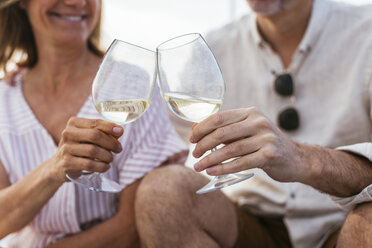 Mature couple drinking wine at sunset on a sailing boat - EBSF02630