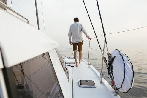 Marure man walking on catamaran, rear view - EBSF02633