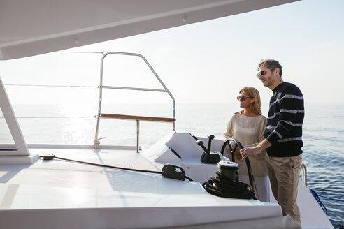 Mature couple navigating catamaran on a sailing trip - EBSF02642