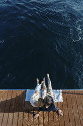 Mature couple sitting on jetty, relaxing at the sea - EBSF02645