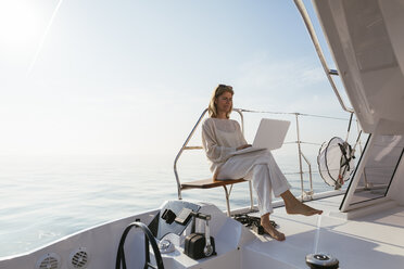 Woman sitting on catamaran, using laptop - EBSF02648