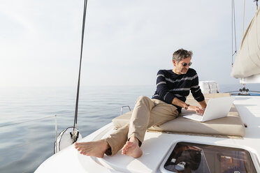 Mature man sitting on deck of a catamaran, using laptop - EBSF02657