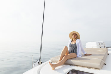 Mature woman relaxing on a catamaran, taking a sunbath - EBSF02660