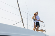 Mature couple making holidays, sailing on a catamaran - EBSF02669