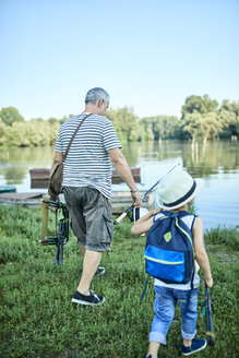 Back view of grandfather and grandson with fishing chair and fishing rods - ZEDF01472
