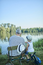Back view of grandfather and grandson fishing togetehr at lakeshore - ZEDF01475