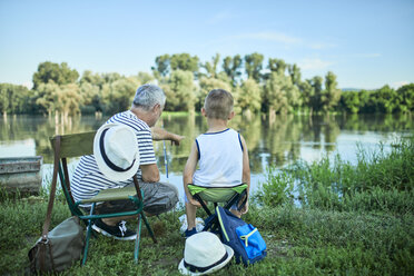 Back view of grandfather and grandson fishing together at lakeshore - ZEDF01478