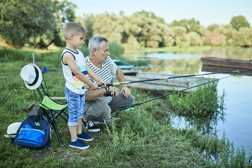 Grandfather and grandson fishing together at lakeshore - ZEDF01484