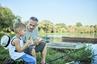 Grandfather and grandson eating sandwiches together at lakeshore - ZEDF01487