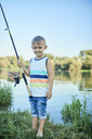 Portrait of smiling little boy with fishing rod at lakeshore - ZEDF01490