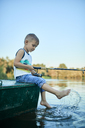 Little boy with fishing rod sitting on boat splashing with water - ZEDF01496