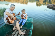 Grandfather teaching grandson playing guitar - ZEDF01499