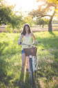 Portrait of smiling girl with bicycle in nature - LVF07304