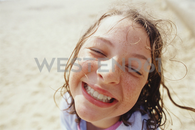 A young girl with a wide grin, eyes half closed, and wet hair outside in the rain. - MINF00331