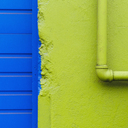 A green painted wall and pipe by a blue doorway. - MINF00340