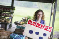 An organic fruit and vegetable farm. A  person carrying a blueberries sign. - MINF00364