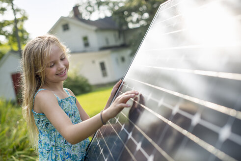 A young girl beside a large solar panel in a farmhouse garden. - MINF00406