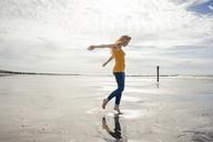 Netherlands, Zeeland, woman dancing on the beach - KNSF04189