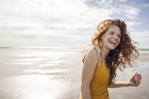 Netherlands, Zeeland, portrait of laughing redheaded woman on the beach - KNSF04192