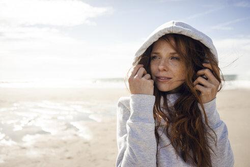 Netherlands, Zeeland, portrait of redheaded woman wearing hooded jacket on the beach - KNSF04195